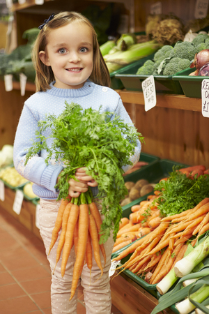 farm shop: Young Girl Holding Bunch Of Carrots In Farm Shop Stock Photo