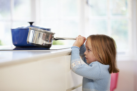 burns: Young Girl Risking Accident With Pan In Kitchen