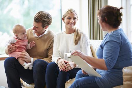 Bezoeker van de Gezondheid Praten met gezin met jonge baby
