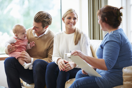 children talking: Health Visitor Talking To Family With Young Baby