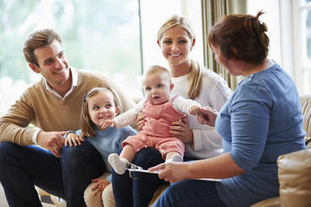family health: Health Visitor Talking To Family With Young Baby