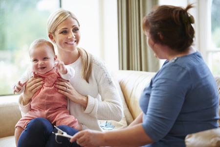 若い赤ん坊と母に話して、健康の訪問者