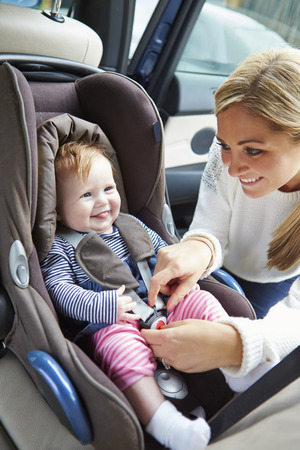 Mother Putting Baby Into Car Seat photo