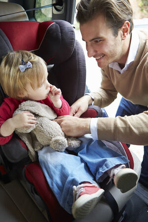 car seat: Father Putting Young Girl Into Car Seat