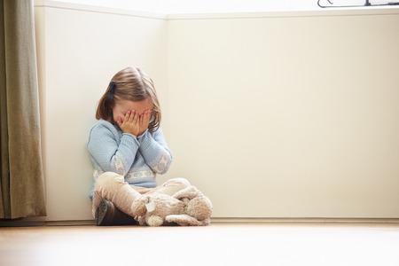 bambini: Bambino infelice seduta sul pavimento in angolo a casa Archivio Fotografico