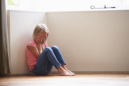 niños sentados: Niño infeliz que se sienta en suelo en Corner At Home