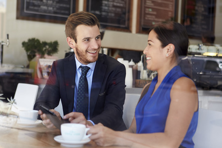 man drinking coffee: Businessman And Businesswoman Meeting In Coffee Shop