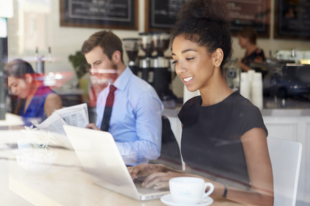 african coffee: Businesswoman Using Laptop In Coffee Shop