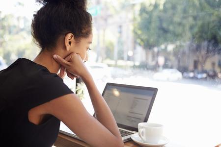 mujer tomando cafe: Empresaria que usa la computadora port�til en Coffee Shop