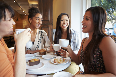 coffee table: Group Of Female Friends Meeting In Caf� Restaurant