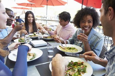 comidas: Grupo de amigos que disfrutan comida en el restaurante al aire libre