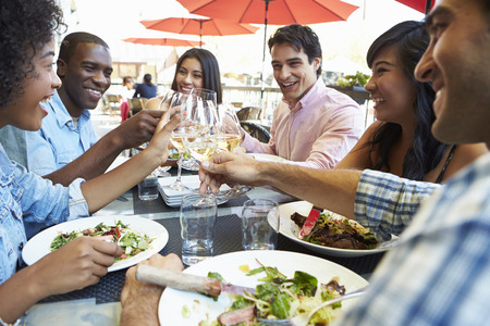 Group Of Friends Enjoying Meal At Outdoor Restaurant photo