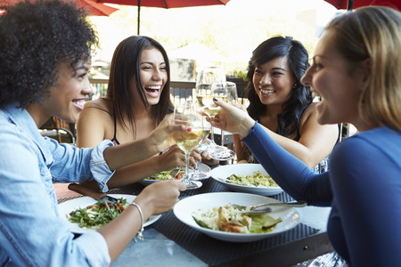 people eating restaurant: Group Of Female Friends Enjoying Meal At Outdoor Restaurant
