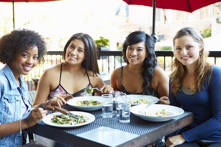 amigos hablando: Grupo de Amigos femeninos que disfrutan de la comida En el restaurante al aire libre Foto de archivo
