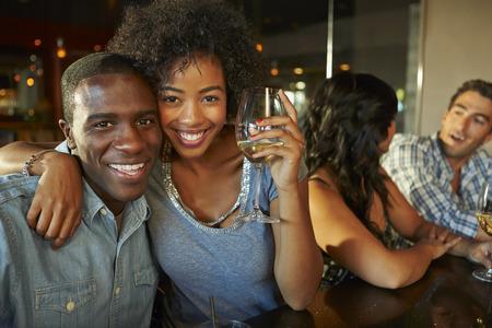 copa de vino: Pares que disfrutan de la bebida en el bar con los amigos