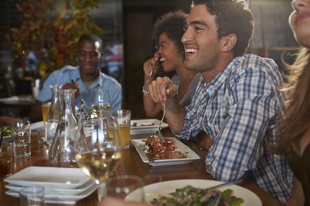 comiendo: Grupo de amigos que disfrutan de la comida en restaurante Foto de archivo