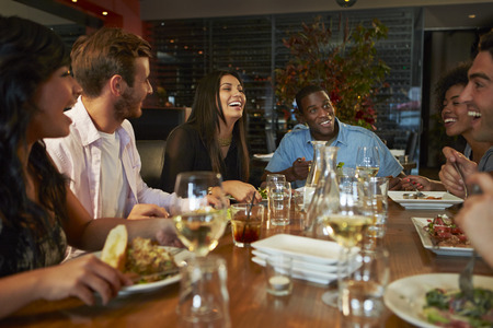 mixed race people: Group Of Friends Enjoying Meal In Restaurant Stock Photo