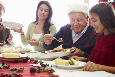 Multi Generation Family Enjoying Christmas Meal At Home