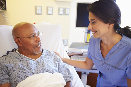 Nurse Talking To Senior Male Patient In Hospital Room photo