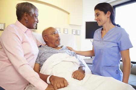 black male: Nurse Talking To Senior Couple In Hospital Room
