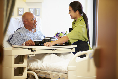 Senior Male Patient Being Served Meal In Hospital Bed photo
