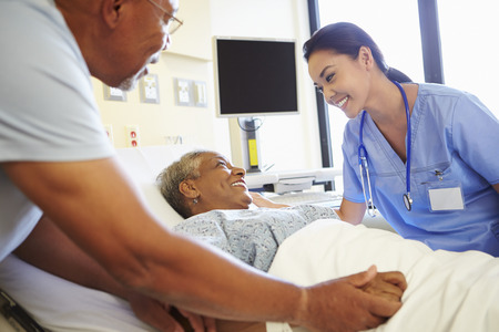 Nurse Talking To Senior Couple In Hospital Room photo