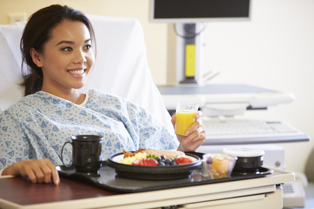 Female Patient Enjoying Meal In Hospital Bed