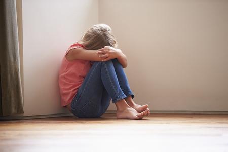 Criança infeliz sentado no chão no canto em casa Foto de archivo