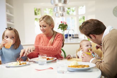 Family With Young Baby Eating Meal At Home photo