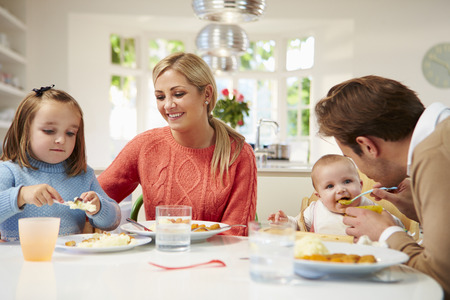 high chair: Family With Young Baby Eating Meal At Home