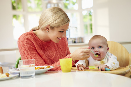 Mother Feeding Baby Sitting In High Chair At Mealtime