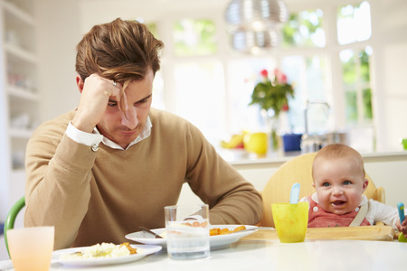 Father Feeling Depressed At Baby's Mealtime Imagens