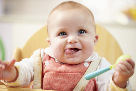 Portrait Of Happy Young Baby Boy In High Chair Stockfoto