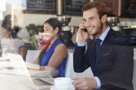 Businessman Using Mobile Phone And Laptop In Coffee Shop photo