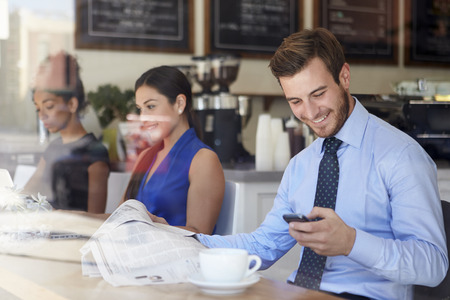man drinking coffee: Businessman With Mobile Phone And Newspaper In Coffee Shop Stock Photo