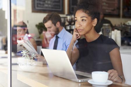 実業家のコーヒー ショップでノート パソコンを使用して