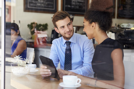 business meeting: Businessman And Businesswoman Meeting In Coffee Shop