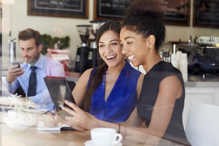 hombre tomando cafe: Dos empresarias Reunión En Coffee Shop