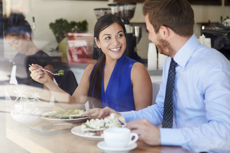 Two Businesspeople Meeting For Lunch In Coffee Shop photo