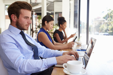 Businessman Using Laptop In Coffee Shop photo