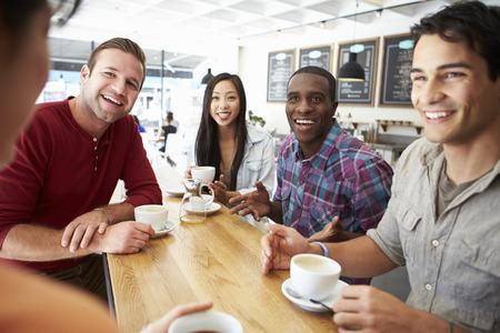 mujer tomando cafe: Grupo de amigos Reuni�n En Coffee Shop