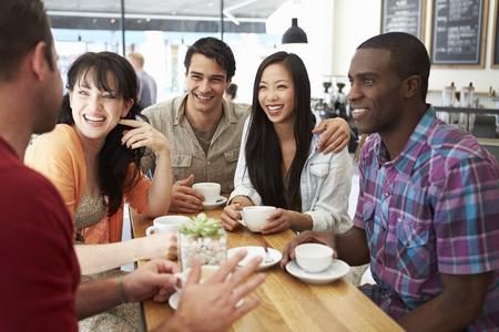 hombre tomando cafe: Grupo de amigos Reunión En Coffee Shop