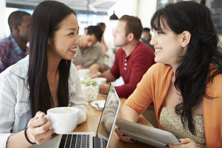 Two Female Friends Meeting In Busy Coffee Shop photo