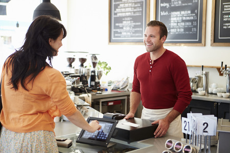 Customer Paying In Coffee Shop Using Touchscreen photo