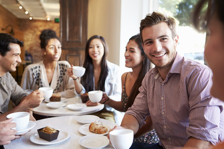 personas tomando cafe: Grupo de amigos Reuni�n En Caf Restaurante Foto de archivo