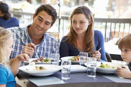 屋外レストランで食事を楽しむ家族