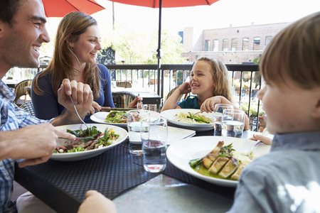 Family Enjoying Meal At Outdoor Restaurant photo