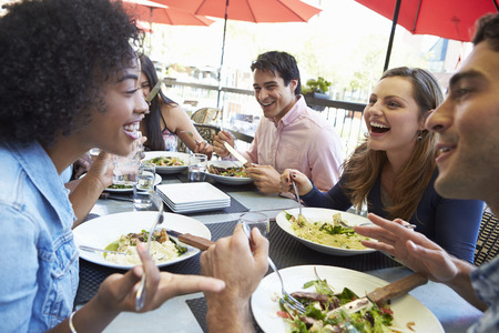 people laughing: Group Of Friends Enjoying Meal At Outdoor Restaurant Stock Photo