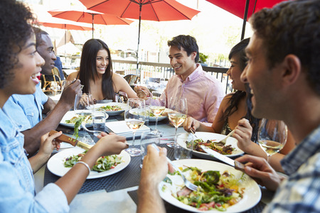people eating restaurant: Group Of Friends Enjoying Meal At Outdoor Restaurant Stock Photo