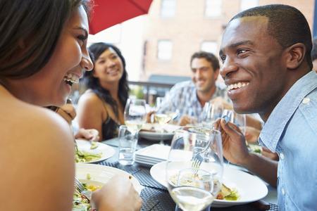 Gruppe Freunde, die Mahlzeit genießen Am Außen Restaurant